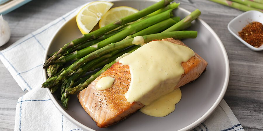Seared salmon and asparagus spears with hollandaise sauce on top.